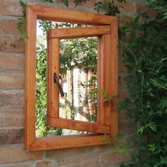 Садовое зеркало на кирпичном заборе в виде окна...